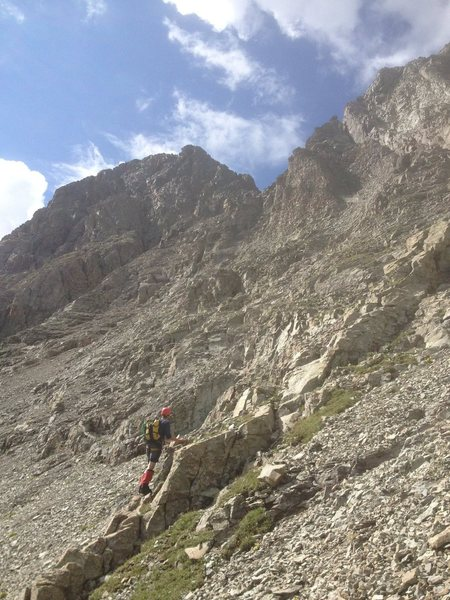 "The middle section of the route, the ""vegetated shelf"" heading towards the red scree shoulder (which is in the notch on the skyline above the climber) on the North ridge.  Summit highpoint on left."