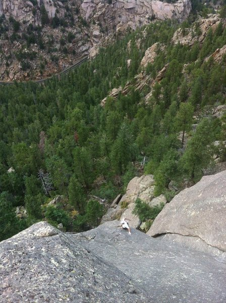 "Eddie climbing through the crux slab of ""Gray Pilgrim"", 5.9+. The highway is just visible way down below."