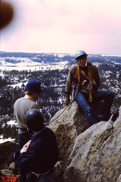 1969 - Devils Tower.  At that time, you had to write ahead and ask for permission to climb, have a letter or two of recommendation, a list of previous climbs, have the ranger check your gear at Park Headquarters, etc., etc.<br> <br> You also had to have helmets - thus a few construction hats and one motorcycle helmet in the picture.  Snowed most of the day but we had driven way to far (Rexburg, Id) to not summit in any way possible.<br> <br> Steve Henderson, Val Price, Kim Miller (with the Millermitts and hammer).  Photo taken by John Ricks - whose parents let us take their Cadillac.