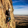 Eddie crimping high over Boulder on the exposed third pitch.<br> <br> South Face of the Maiden, CO.