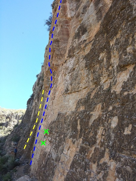 Blue line is approximate route line. Belayer in picture and yellow line are on the climb to the left (unlisted 11d) and two green Xs mark bolts on the climb to the right (unlisted 10b). Looking from the right (South-ish) of the climb.  At the bottom of the photo, you can see the hand-line. Sorry for the crappy picture!