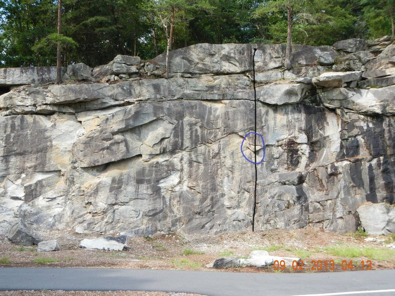 "This shows the route before the ""step"" was removed. The route was more of a 5.9/5.9+ with the step as it allowed the climber to stand up high enough to reach the holds above the current crux. Try to start directly underneath the rings rather than using the easier corner to the left."