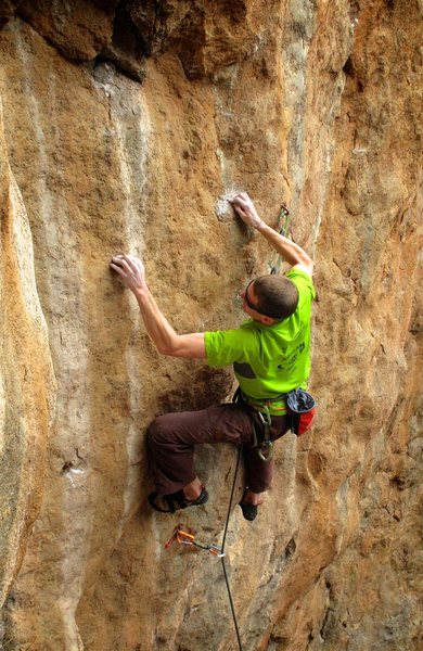 "Crimping hard on ""the Piranha"" hold on the lower crux. My left hand isn't really on a hold. Heath Bailey photo. February 2014."