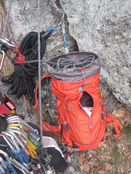 Solo climbing gear management with bag as rope tote, clipped at belay station.