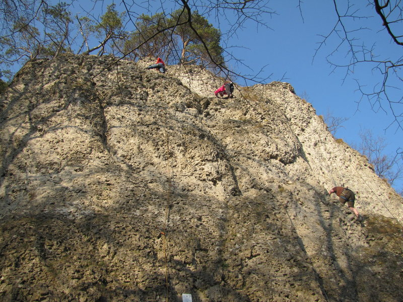 The woman in pink is near the top of Stier. Her rope traces the run of the route.