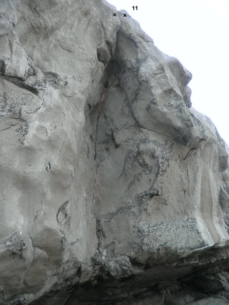 Eleventh route from left to right. Top rope anchors only. The route should follow the cavity on sloppy holds to a chimney kind of route