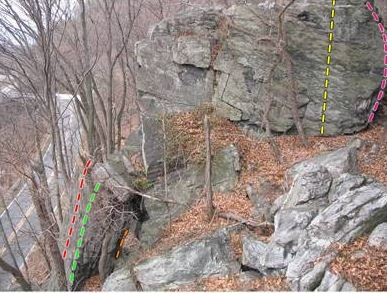 The slab/face on the rock in the upper right corner of the photo is The Company Store (yellow line). The arete to the right is Mule Powered (pink line). To the right of Mule Powered would be Nancy.<br> In the bottom left of the photo there is Pocket Slab (red line), Bass Rock Bums(green line), and a short orange line shows a tiny visible section of The Secret Six.