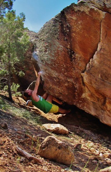 Sticking the arete's pinch on Pyrrhic Pulse. From there, switch the hand to an undercling and throw big to a sharp edge.