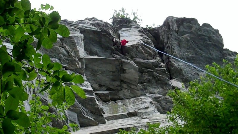 Climber wrapping up at the top of Nutsweat, just past the final roof move.