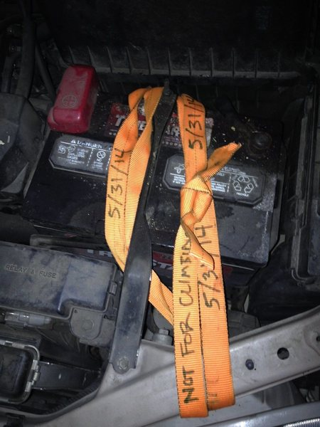 Webbing wrapped over top of 2002 Toyota Sienna battery