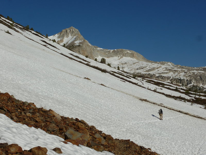 Jeff on west snowfields on shoreline of Saddlebag Lake, with North Peak finally coming into view.