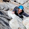 Pulling the crux P1 flake (Eric Isaac climbing).