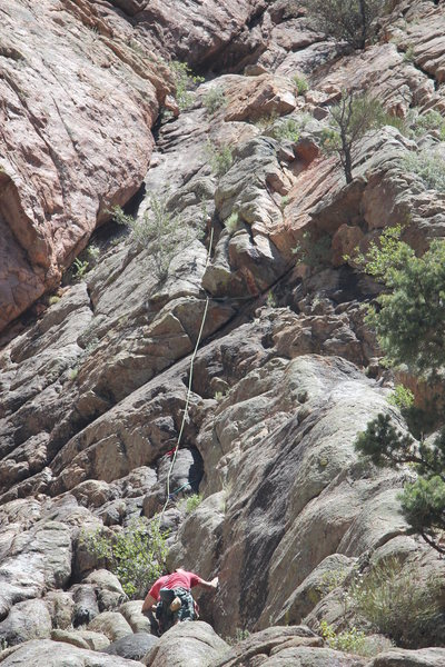 The climber is sitting at the belay on top of the first pitch, and the rope shows the way to go on the second pitch.