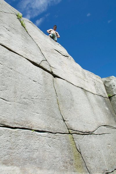 Catching a breather on top of this high boulder problem.