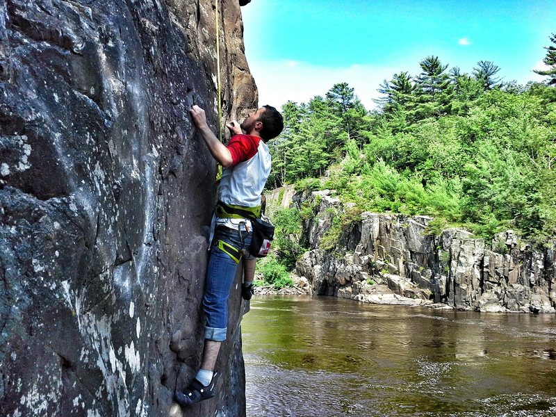 Taylor's first day of outdoor climbing in MN@SEMICOLON@ halfway up Iron Ring aka Witches Tit on Angle Rock on a perfect July day.