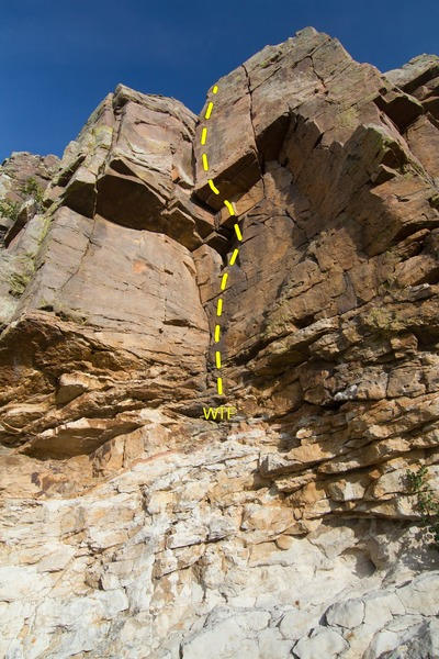WTF starts just above the rotten band of rock and climbs up the center using the face holds and corner crack with a possible variation using the thin crack just to the right of the corner.