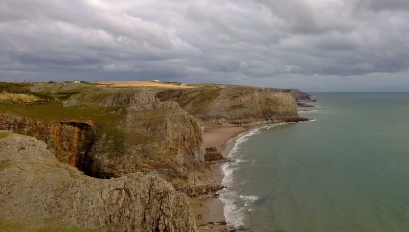 Looking East from Fall Bay. Typical Gower scenery: sandy beaches, limestone cliffs and a cloudy sky.