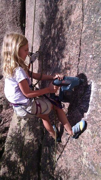 Norah drilling the last bolt on a new climb.