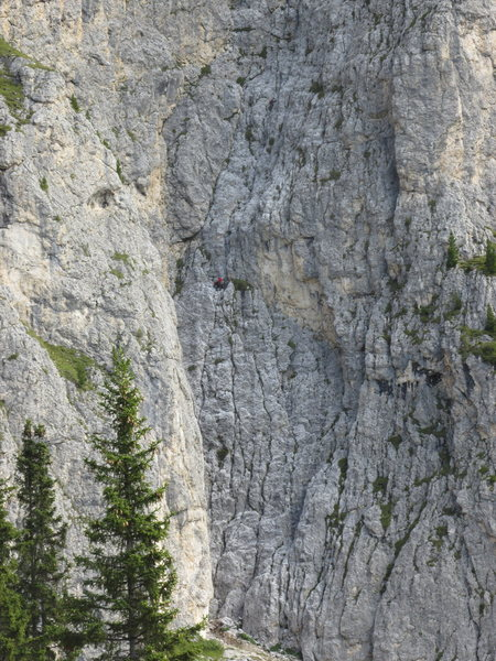 Two climbers visible on first belay ledge; third climber is nearing the second belay stance.