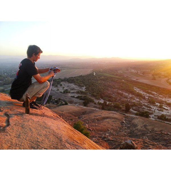Jesse Morelock setting up toprope for The Eye and Unisloper on top of the Joe Brown Boulder at Sunset