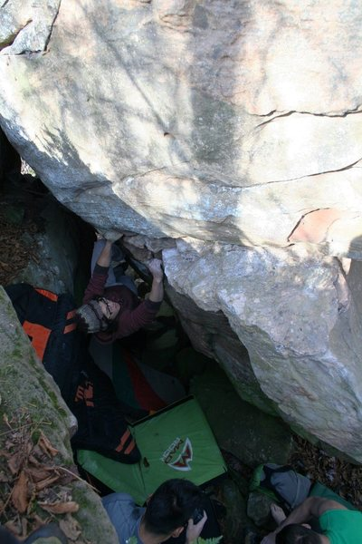 Boris on V2ish problem. Don't know what this is called or how to describe getting there. Uphill and right of Warmup Wall. Sit start and traverse up and right, eventually around arete for top out. Needs several pads or spotter to move single pad (or, just don't fall). Very fun problem in a very weird spot. Stays wet longer than most other problems due to location. Do not climb wet rock here.