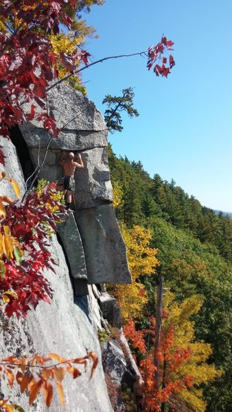 Climber getting ready to step out onto The Arete on a hot fall day with some foliage starting to show.