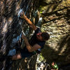 Oliver Hill setting up for the crux move on Wild Yet Tasty.