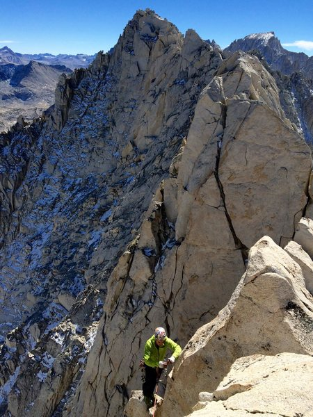 Johnny K topping out on the route/ridge, with the true summit of Ruby Peak in the background.
