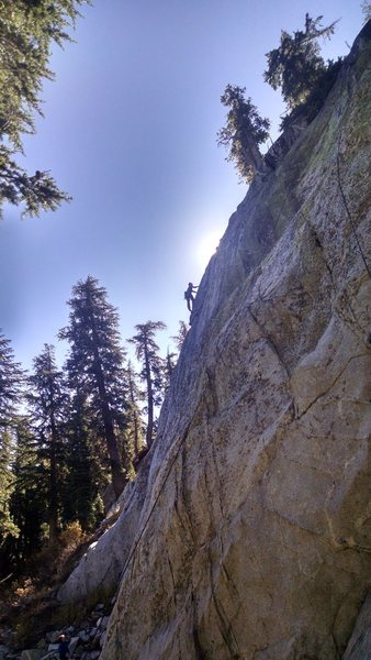 Justin Colville reaching up on the exposed arete on the second ascent