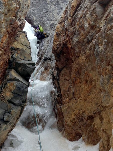 """Kevin Hansen, grappling with the """"snow chockstone"""" which is mostly hidden from view."""