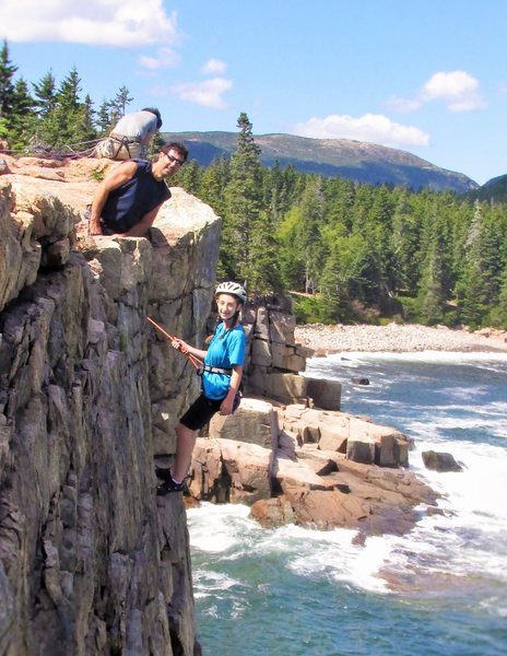 Dad and Daughter Climbing Otter Cliffs 2014. With Dorr Mnt. in the back-round and waves crashing below, this makes for a very dramatic photo.