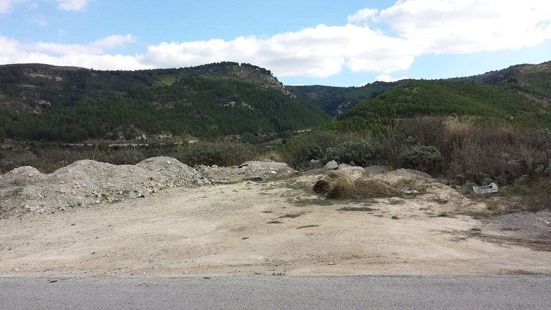 This is what the small parking area looks like from the road SP5.  The crag is the rock face down below.