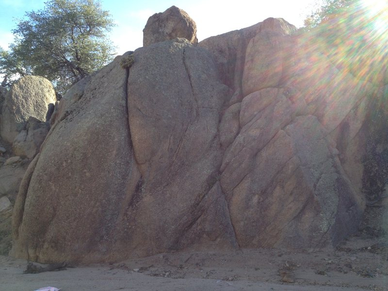 Large boulder in the wash to the West. Routes unknown.
