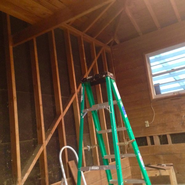 "I cut away a chunk of the ""attic"" above the garage to get more height and stripped the wall boards to reveal the studs."