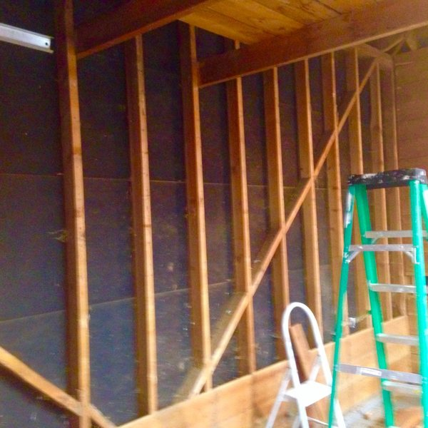 """I cut away a chunk of the """"attic"""" above the garage to get more height and stripped the wall boards to reveal the studs."""