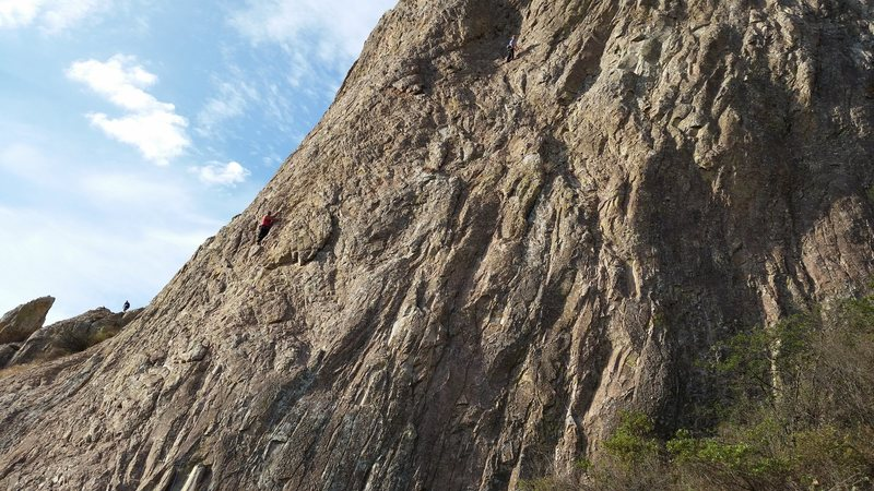 A view of a portion of the south face of Pena de Bernal. The left climber (in the red shirt) is on P1 of Bernalina@SEMICOLON@ the climber up and right (in the blue shirt) is atop P1 of Via del Padre.