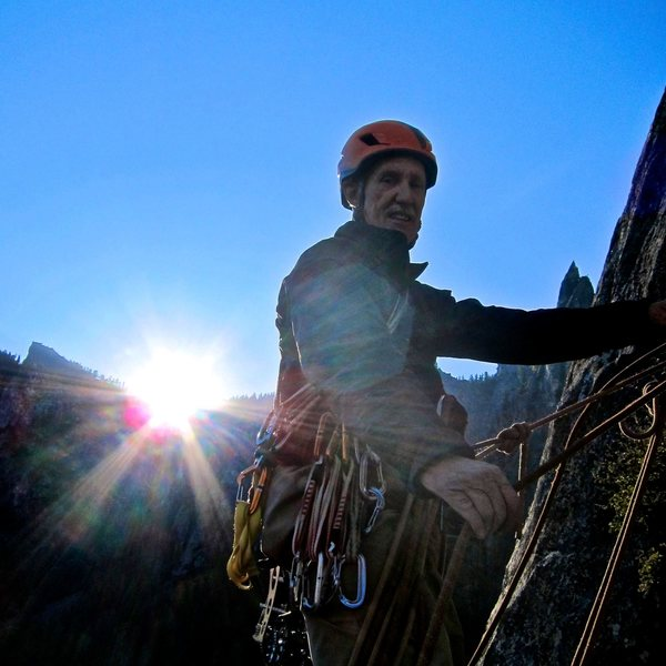 David belaying with the sun rising in the background.