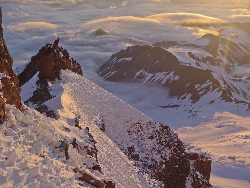 Joe traversing sun cupped snow slopes to pass the prominent gendarme on Curtis Ridge.