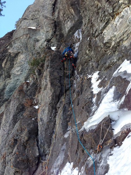 Eric Wright leading first pitch in early Feb 2015.<br> <br> Photo by Ozman.<br> <br> This is a classic sketchy, somewhat rotten mixed pitch; however, the struggle to reach the upper ice pitch feels a bit contrived in that one can scramble up easier ledges 20-30 ft left in the photo to avoid this difficulty. Then of course one would miss all this icy mixed bit.