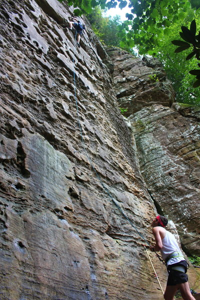 Belayer observes as climber leads the final moves