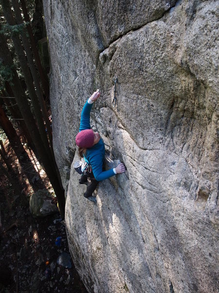 "Caitlin clipping the last ""easy"" bolt before launching into the sustained traverse to the finish"