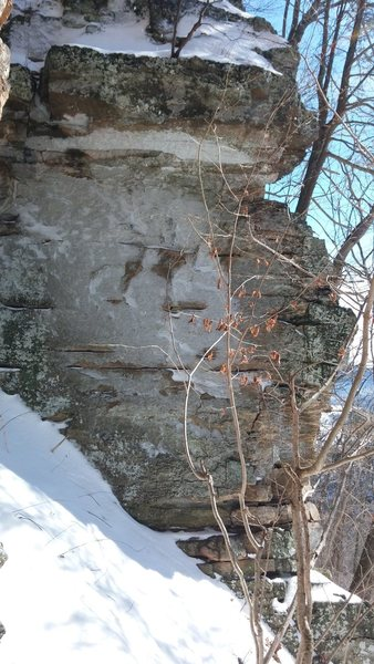 Horrible photo, but may help you find route. Climbs middle of face to nearly indiscernable overhang at 3/4 height. Snow on hillside demonstrates why this would not make a good boulder problem!