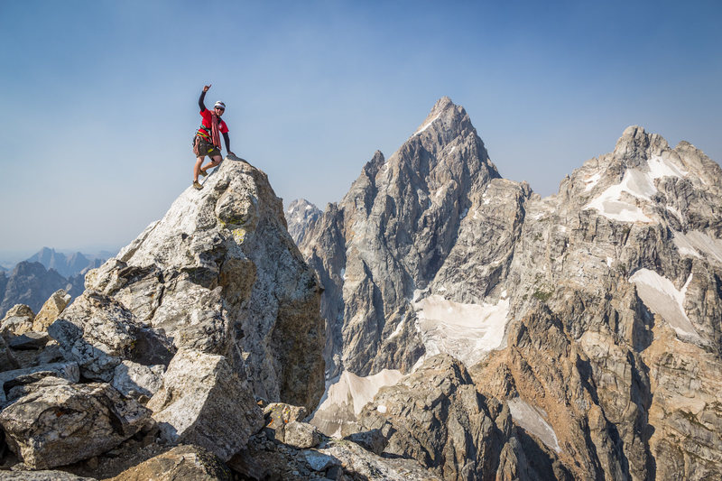 Reaching the summit of Teewinot, with the imposing North Face of the Grand Teton in the background.