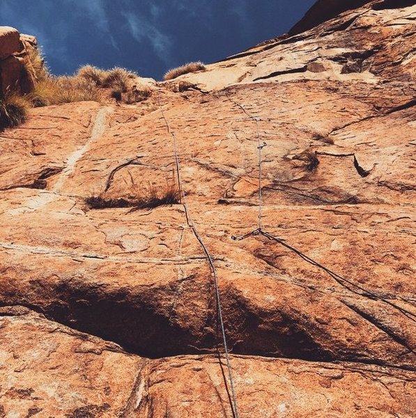Looking up at Left Longing. Like my route comment, you need a piece of gear when crossing over from last bolt to the crack to the anchors. I ran this out as it seems to be about 5.6 at that point.