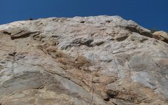 To the left of Enter Slabman. Center of rock directly below anchors.  Crux is mid-point (slick rock)- maybe 5.7 there.