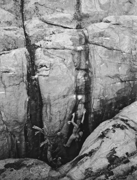 Mike Gasch climbing out of the chasm on the 2nd ascent of Voodoo Blues, 1999.<br> <br> Wide Open Gasch  V8-9 is the chalked line of crimps to his right. Black Magic is the streak to the left.