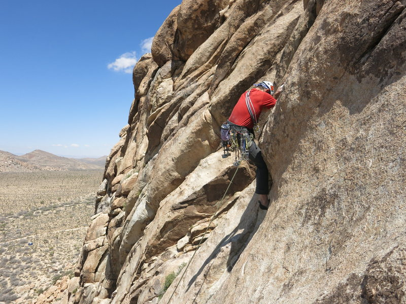 Clay Trager high-stepping the bulge near the end of pitch 3.