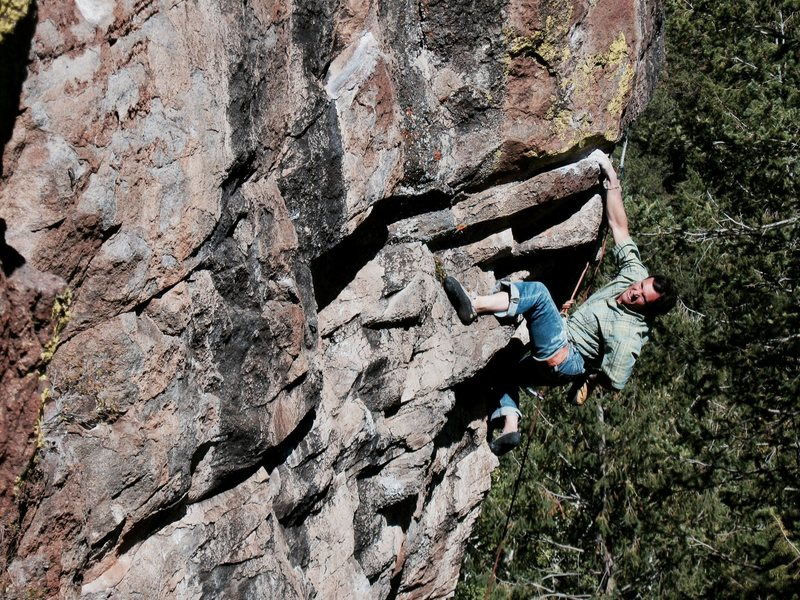 Colin unloading before the final boulder problem which guards the anchor on Burning Point .12b, The Peak's Crag.