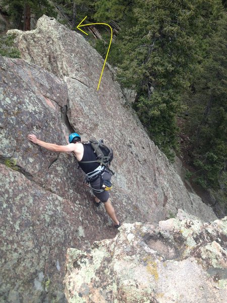 From the top, you can scramble north around where the arrow points, no downclimbing or rapping is necessary, just walk down the boulders to the ground.