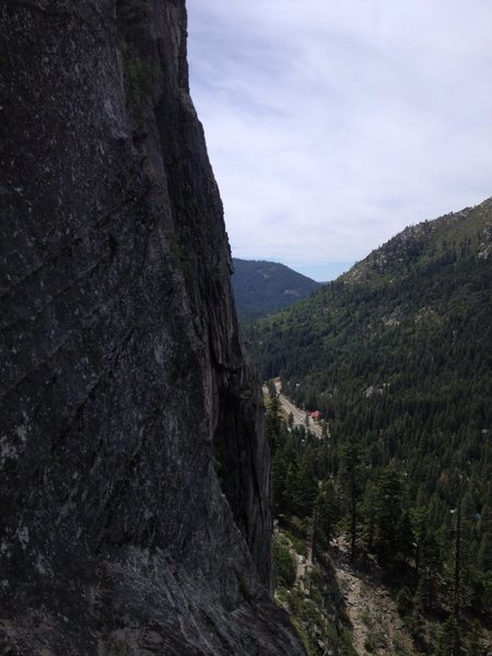 The traverse from North Face anchors. Down and to the right, then up the featured column to the bushy ledge.